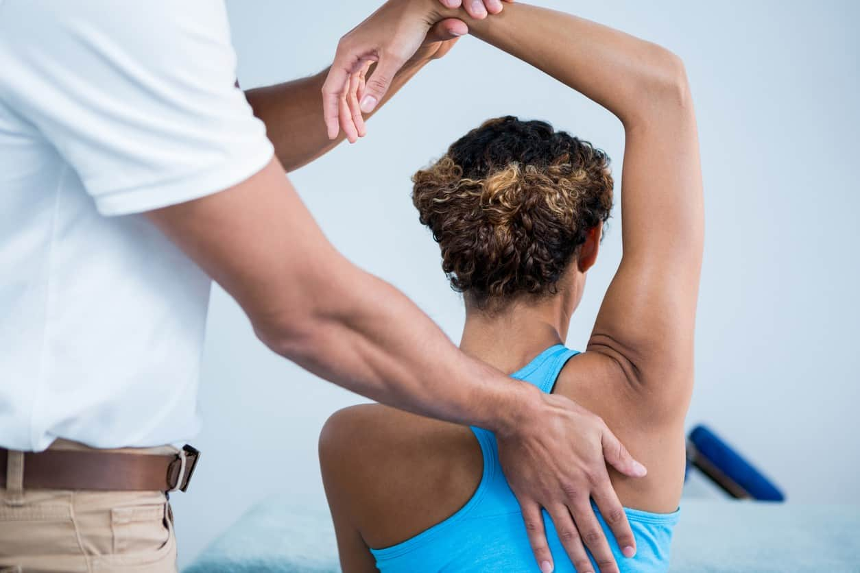 Physiotherapist giving shoulder therapy